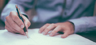 Man holding a pen while drawing up a lease