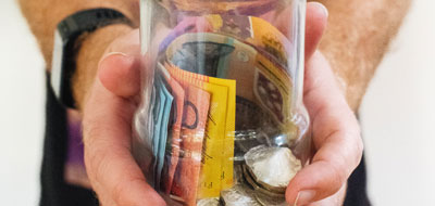 Man holding a jar full of Australian money, notes and coins.