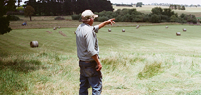 Farmer looking and pointing out across his rural property