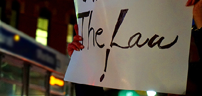 Person holding up a paper sign 'The Law!'