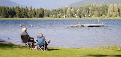 Man and woman sitting in deck chairs overlooking a lake