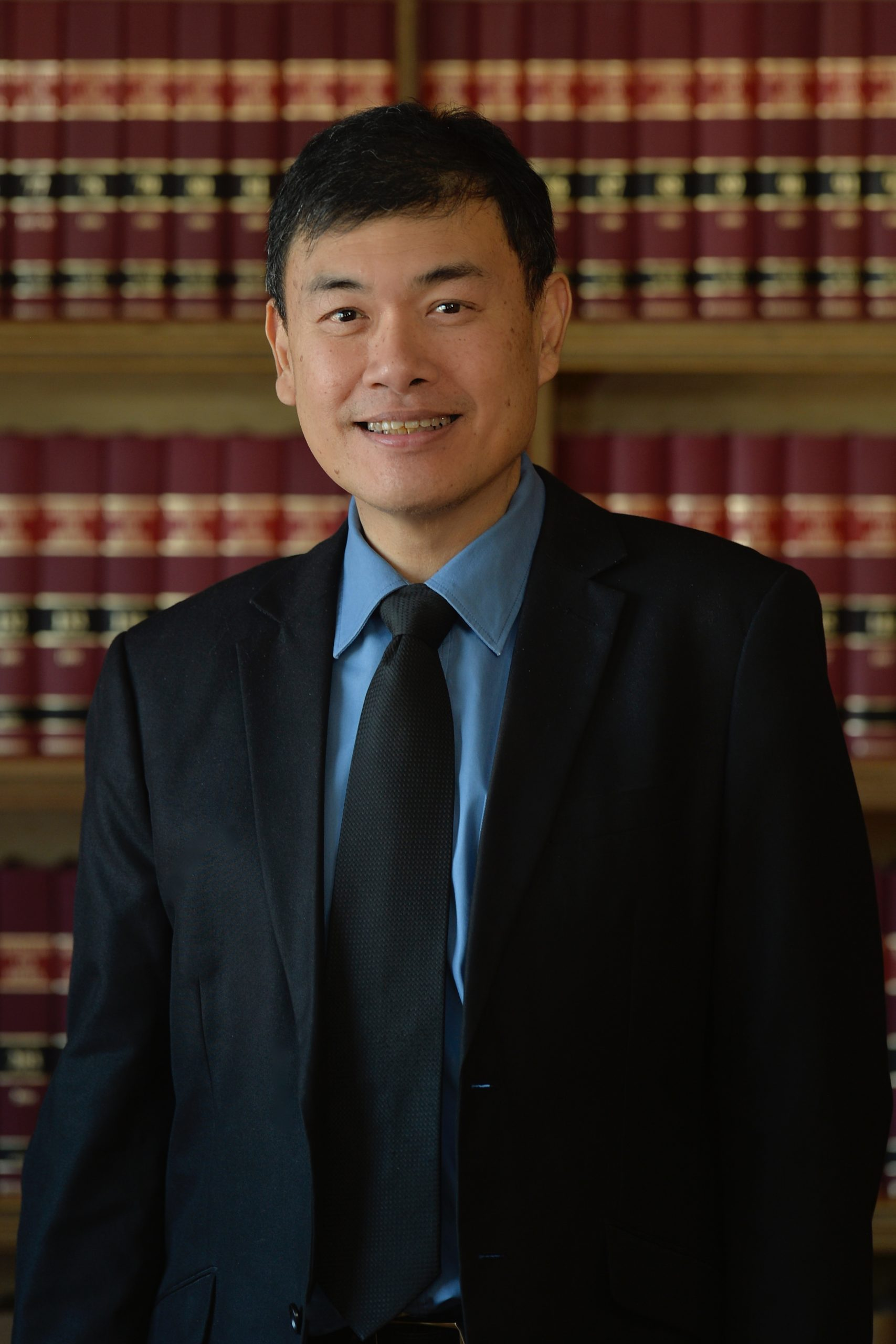 Boon Kim Gwee standing in front of bookcase full of law books